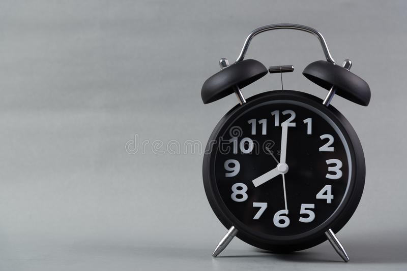 Black color vintage alarm clock on grey background, wake up time stock photos