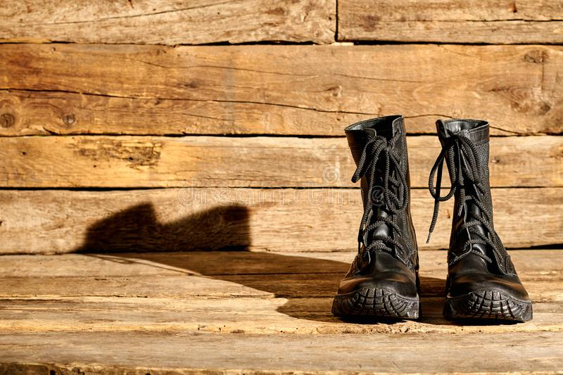 Black combat army boots on wood. Shiny shoes with shadow royalty free stock photography