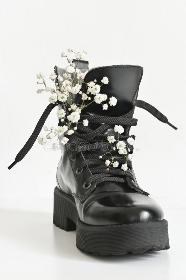 Black combat boot decorated of flowers. Black combat boot decorated of gypsophila flowers on white background royalty free stock photo
