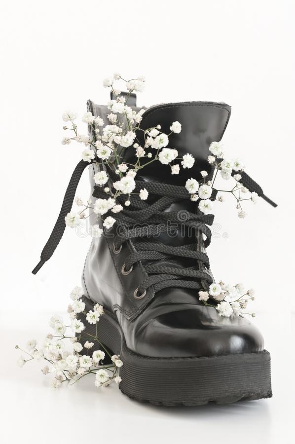 Black combat boot decorated of flowers. Black combat boot decorated of gypsophila flowers on white background stock image