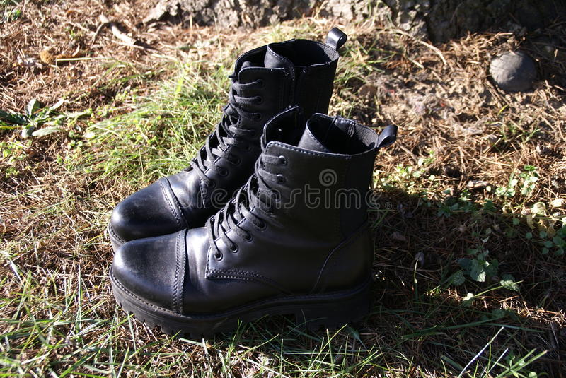 Black combat boots on grass stock photos