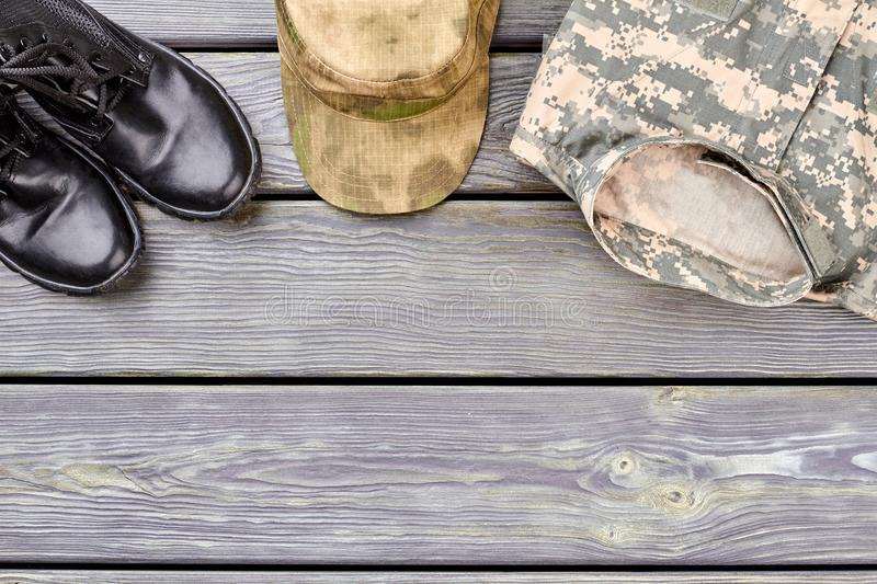 Black combat boots, military cap and clothes. Wooden desk surface background royalty free stock images