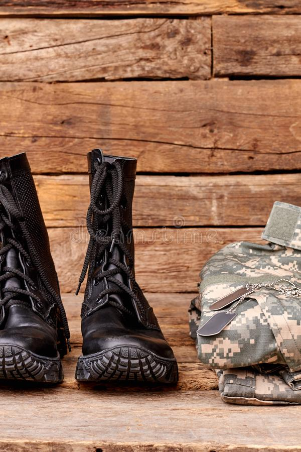 Black combat soldiers boots and clothes. Wooden desk background royalty free stock photos