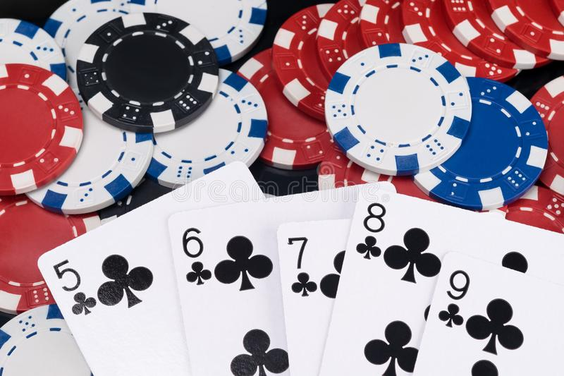 Black combination of winning poker cards against a background of multi-colored casino chips stock image
