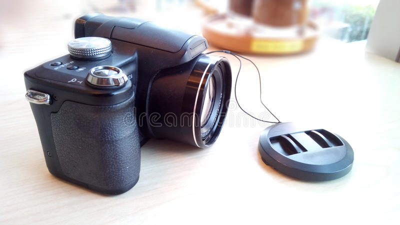 Black compact camera. The old digital camera on wooden table side of glass window royalty free stock photos