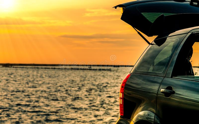Black compact SUV car with sport and modern design parked on concrete road by the sea at sunset. Environmentally friendly. Technology. Road trip travel on stock photos