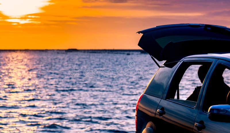 Black compact SUV car with sport and modern design parked on concrete road by the sea at sunset. Environmentally friendly. Technology. Road trip travel on royalty free stock photo