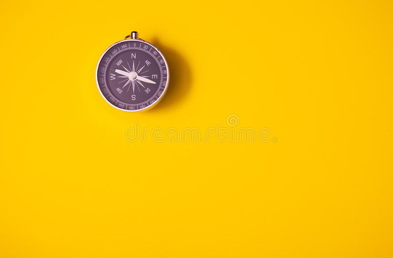 Black compass on yellow background, equipment for travel, tourism and business, top view and copy space stock images