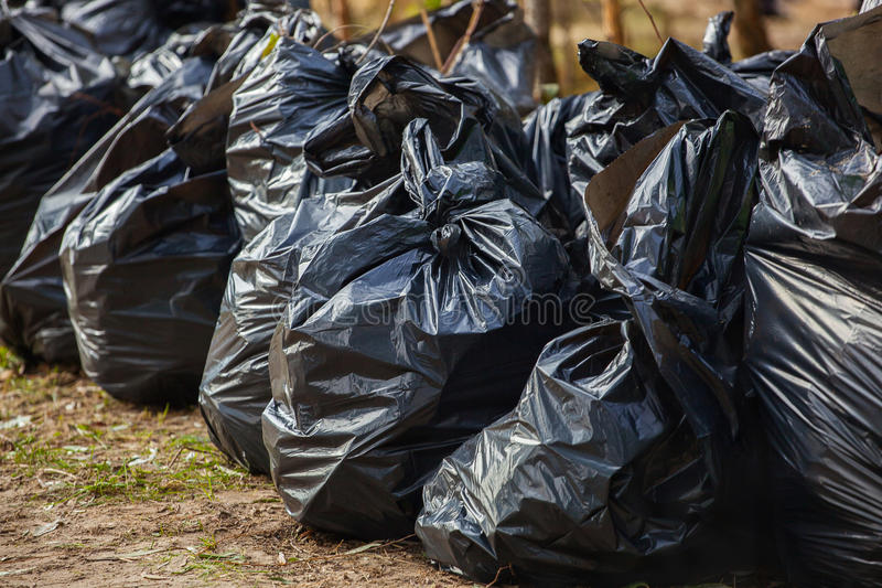 Black, complete and tied garbage bags standing together on the street,. Outdoors. removal, sorting and recycling rubbish stock photo