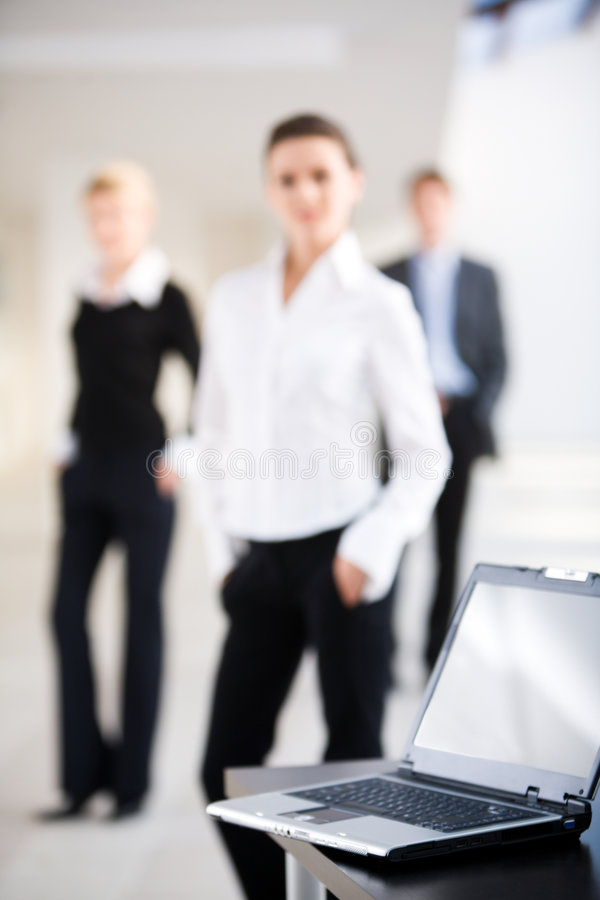 Black computer. Image of black computer lying on the table on the background of three people