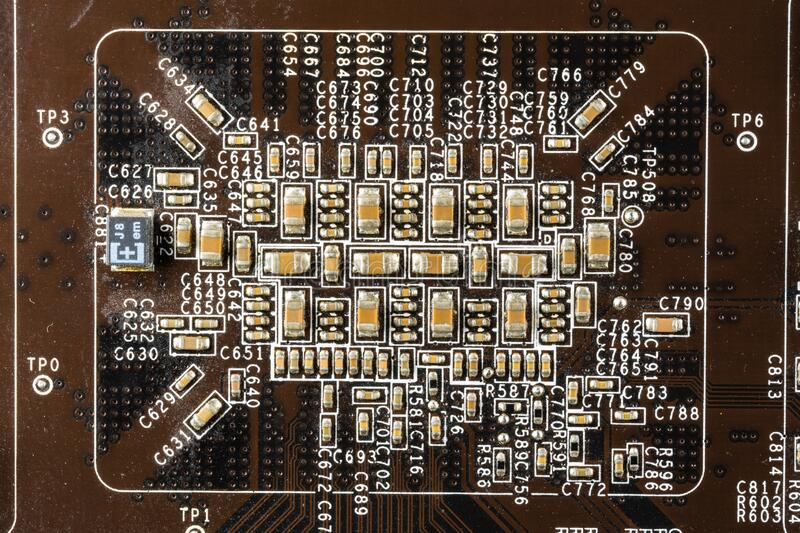 Black computer video card board with brown microcircuits and various electronic components, top view. Macro photo royalty free stock photo