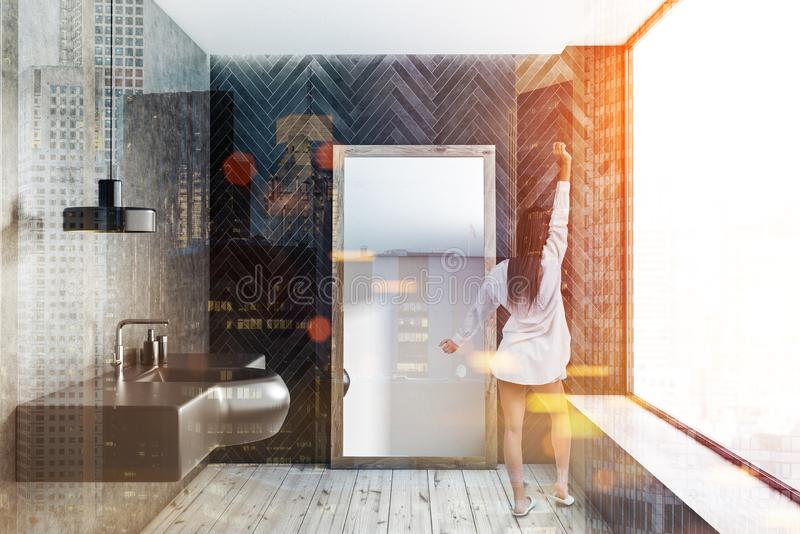 Black and concrete bathroom, sink and mirror, girl. Woman in interior of modern bathroom with black wooden and concrete walls, wooden floor, panoramic window and stock image