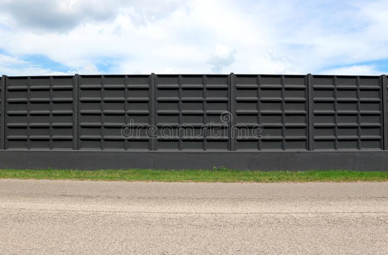 Black concrete surrounding wall with stripe of grass and an asphalt road in front. Cloudy sky above. Background for copy space stock photography