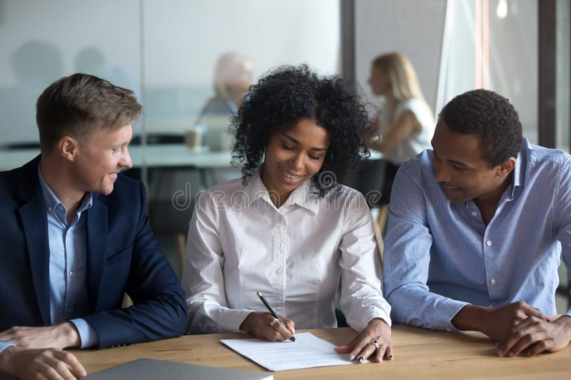 Black confident woman sitting with business partners signing contract royalty free stock photos