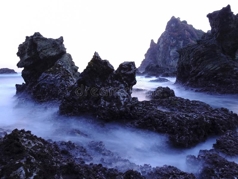 Black Coral Rock and Smooth Waves Watulumbung Beach. Black coral rock and the smooth waves of Watulumbung beach. Favorite spot for landscape photographer stock photos