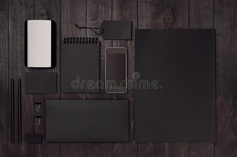 Black corporate stationery, branding mockup set with phone, coffee on dark wood board. Modern stylish male work place. stock image