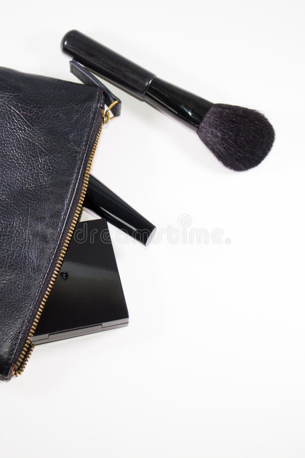 Black cosmetic bag and various makeup products on white background with soft shadows. Black cosmetic bag with various makeup products on white background with royalty free stock photo