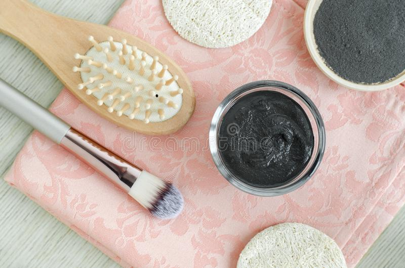 Black cosmetic clay face mask/body wrap in a small glass bowl. Homemade cosmetics. Top view. Black cosmetic clay face mask/body wrap in a small glass bowl stock photo