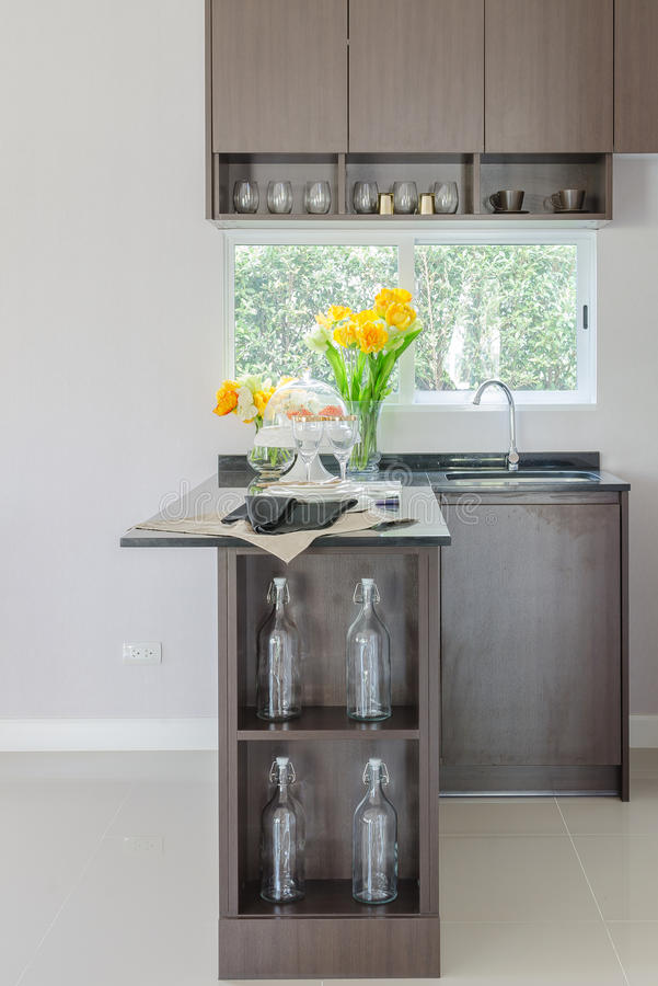Black counter in pantry with vase of plant and modern sink stock photography