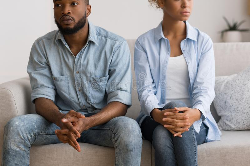 Black Couple Avoiding Eye Contact After Quarrel Sitting On Couch stock photo