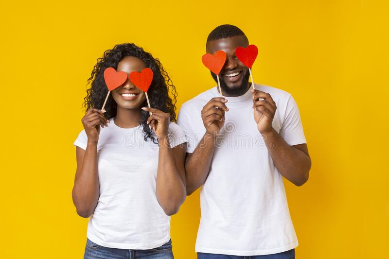 Black couple closing eyes with red love hearts. African american romantic couple closing eyes with red love hearts, yellow studio background royalty free stock photography