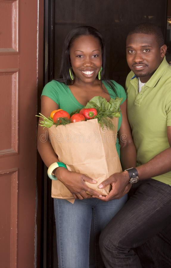 Black couple coming with groceries shopping. Young ethnic African American couple coming back home, returning from store with paper bag full of vegetables royalty free stock photography