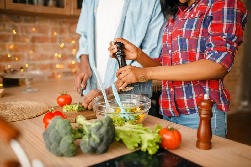 Black couple cooking together on the kitchen. African family preparing vegetable salad at home. Healthy vegetarian lifestyle royalty free stock photo