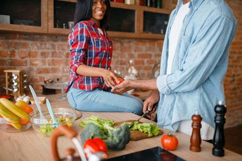 Black couple cooking together on the kitchen. African family preparing vegetable salad at home. Healthy vegetarian lifestyle royalty free stock images
