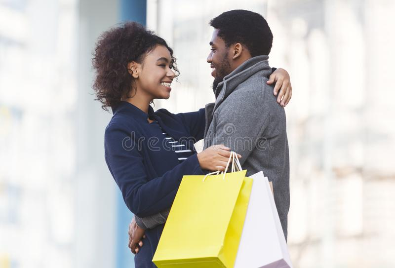 Black couple cuddling in the street after shopping royalty free stock photos