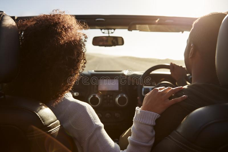 Black couple driving, her hand on his shoulder, back view stock image