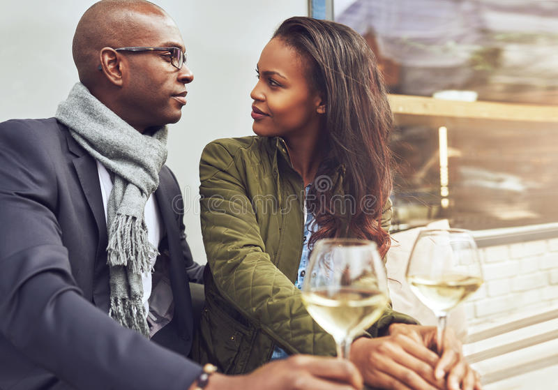 Black couple having a conversation. At a cafe outdoors in the spring stock image