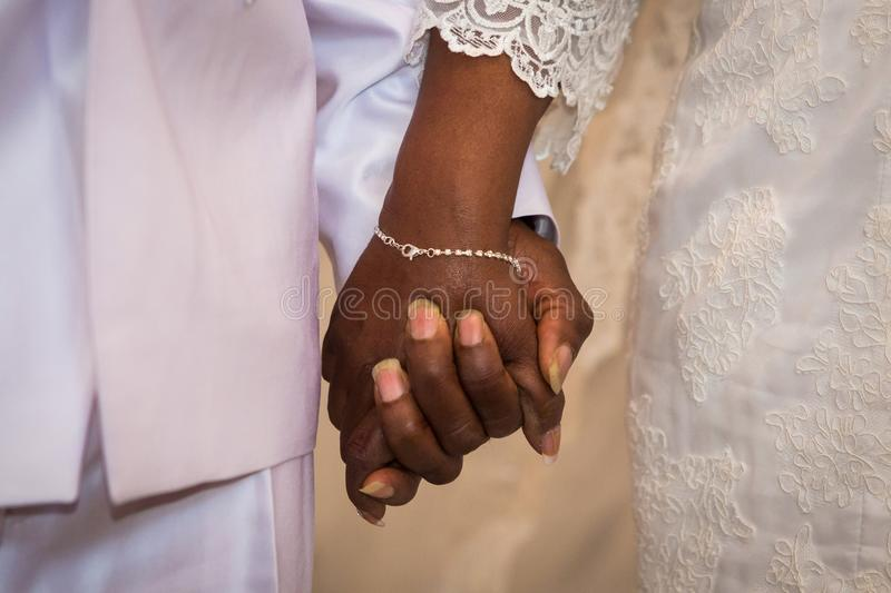 Black couple holding hands during marriage stock photo