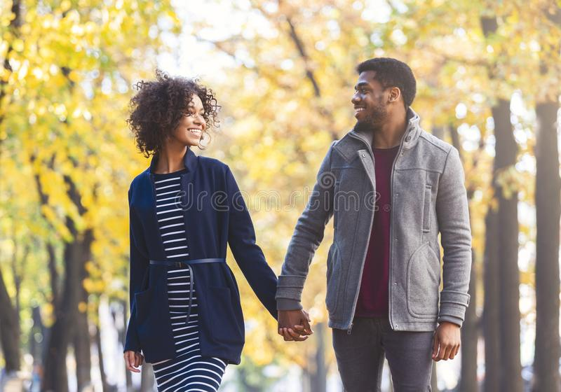 Black couple holding hands while walking by autumn park stock photos