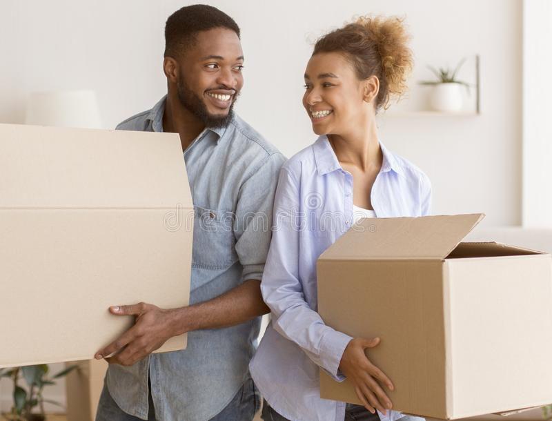 Black Couple Holding Moving Boxes Standing Back-To-Back In New Home. Moving House. Happy Black Couple Holding Packed Boxes Smiling Each Other Standing Back-To royalty free stock photography