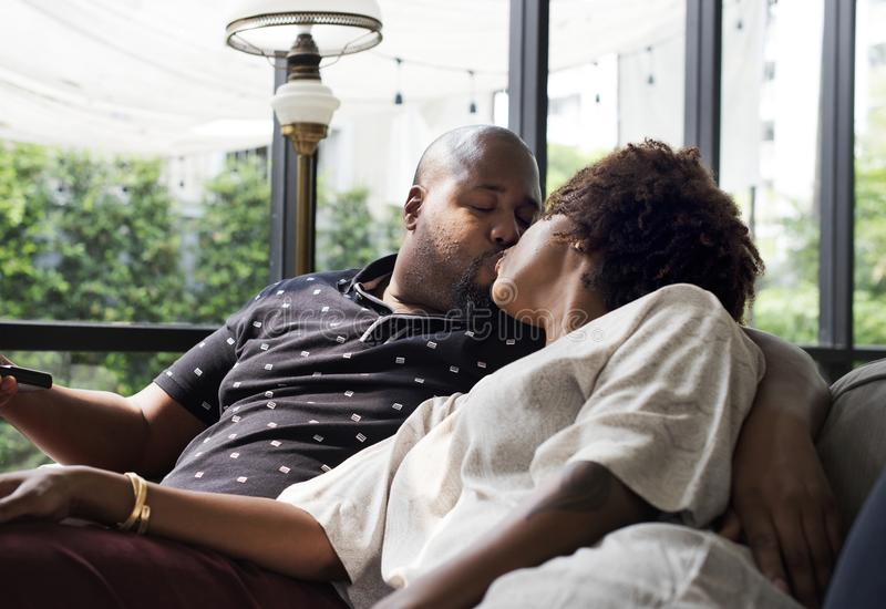 Black couple kissing on the couch royalty free stock photography