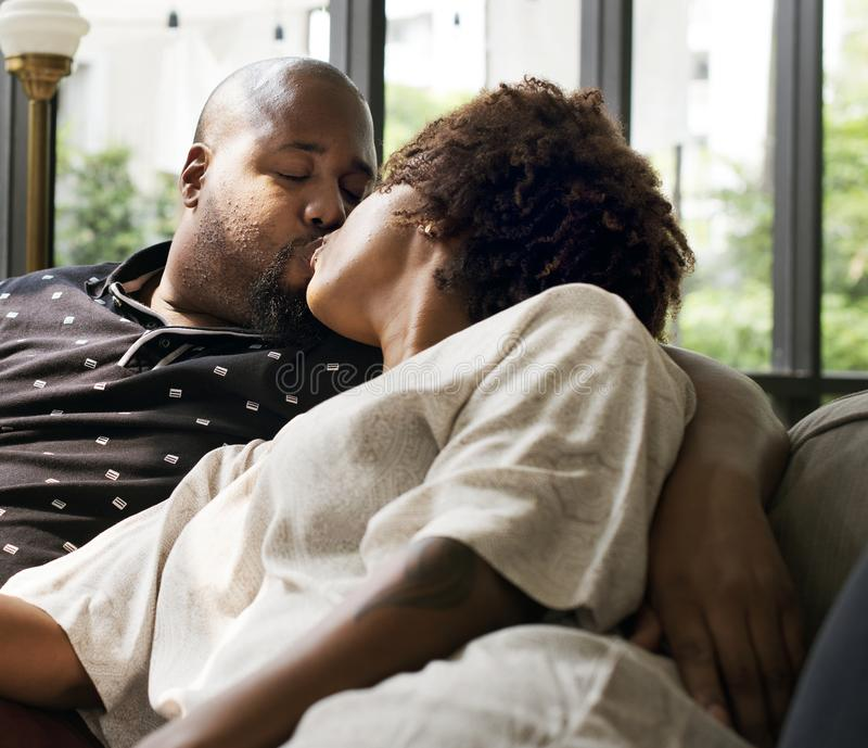 Black couple kissing on the couch royalty free stock image