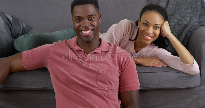 Black couple relaxing on couch and smiling at camera. Young black couple relaxing on couch and smiling at camera royalty free stock photos