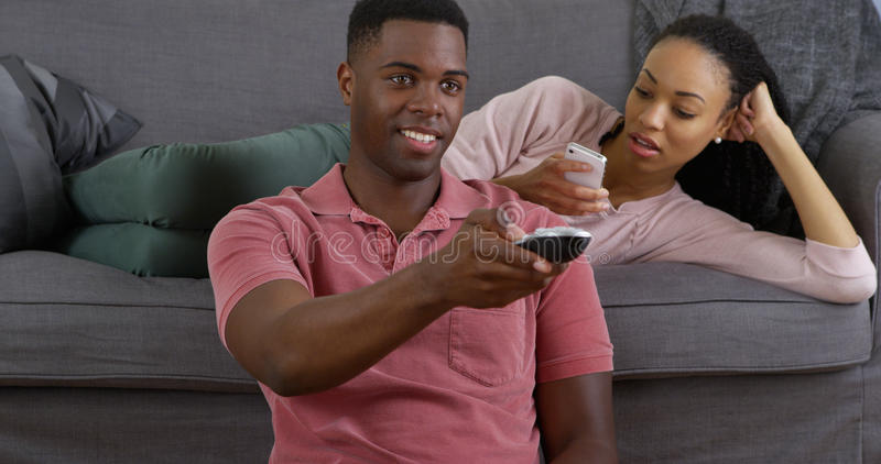 Black couple relaxing at home. Young black couple relaxing on couch with smartphone and watching tv stock photo