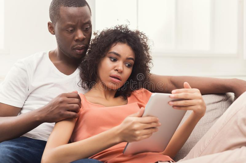 Black couple using digital tablet at home royalty free stock photography