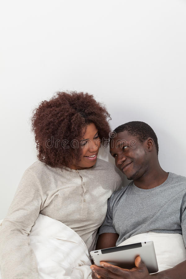 Black couple using the ipad. Young couple in love using the ipad stock image