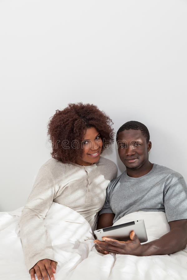 Black couple using the ipad. Young couple in love smiling at camera royalty free stock photography