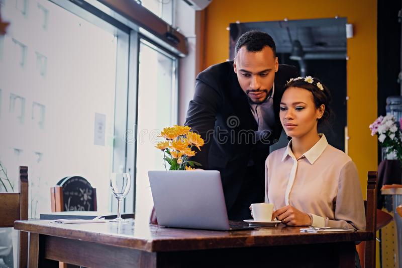 Black couple using laptop in a cafe. royalty free stock image