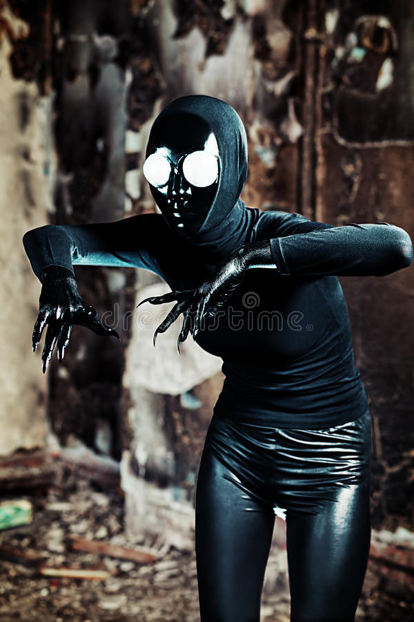 Black creature. Scary alien creature in an abandoned house. Halloween, horror royalty free stock image