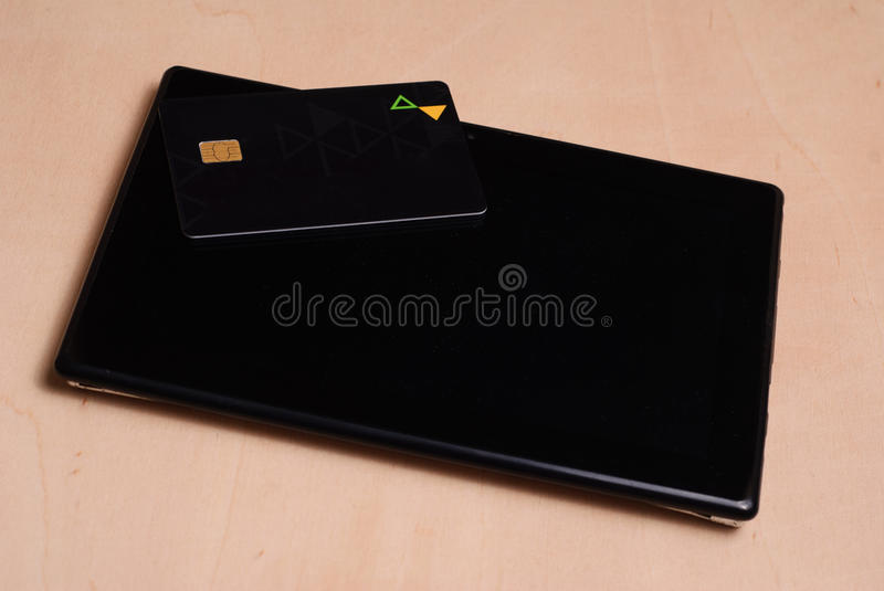 Black credit card is on a black electronic tablet, stock photo