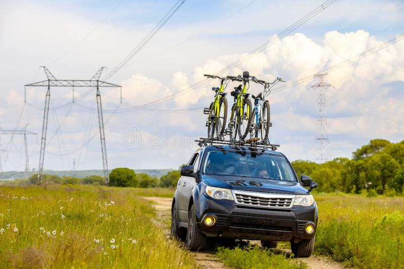 Black crossover with three bicycles on roof rack. In a meadow royalty free stock photo