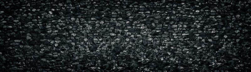 Black crushed granite stone wall wide texture. Angular rock surface panorama. Dark panoramic background royalty free stock photos