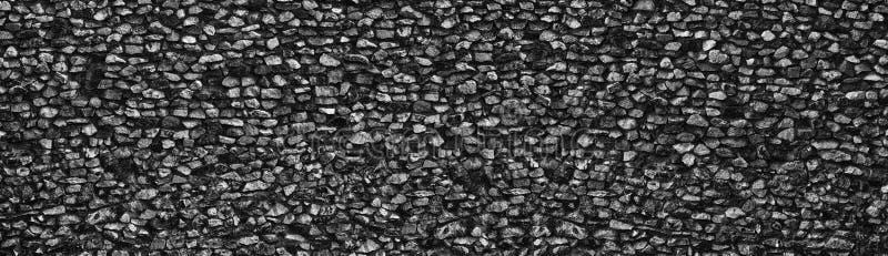 Black crushed granite stone wall wide texture. Rough rock long backdrop. Dark grey panoramic background stock photo