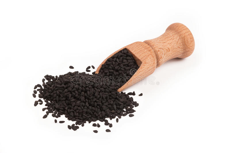 Black cumin seed in wooden scoop isolated on white background. Top view, Nigella sativa royalty free stock image