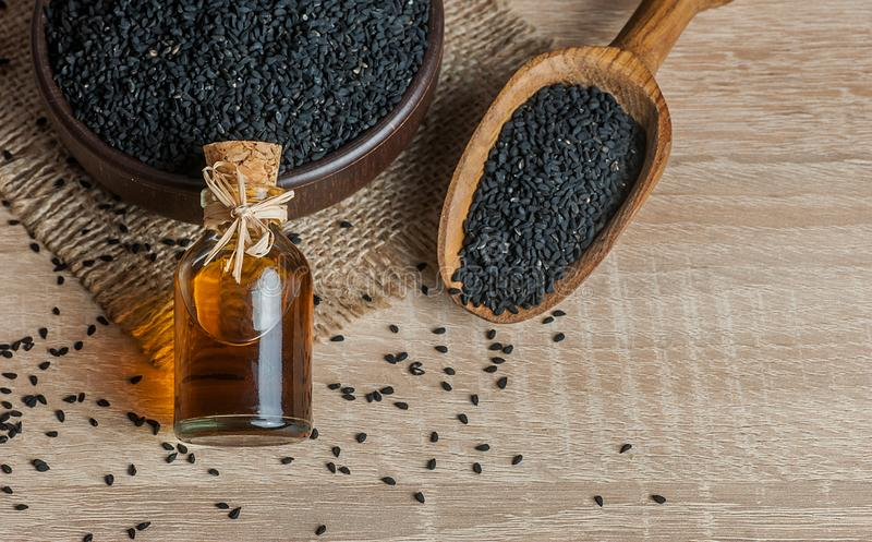 Black cumin seeds and essential oil with bowl and wooden shovel or spoon royalty free stock images