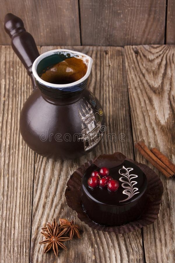 Black cup of coffee with chocolate cake, cinnamon and anise on wooden background. Food. Rustic. Brown royalty free stock images